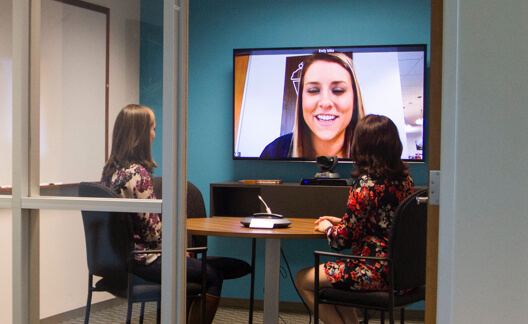 Three person video conferencing meeting in Lifesize huddle room.